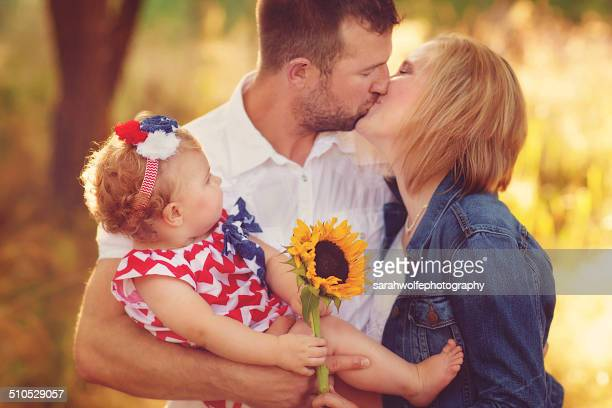 Man holding his daughter and kissing his wife