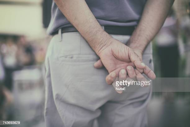 Man holding his hands behind his back