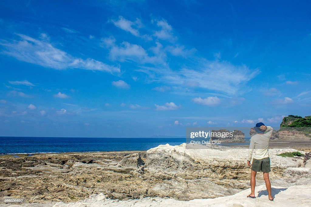 Man holding his hat looking at the beach shore : Stock Photo