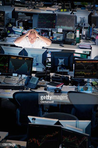 Man holding his head in front of computer