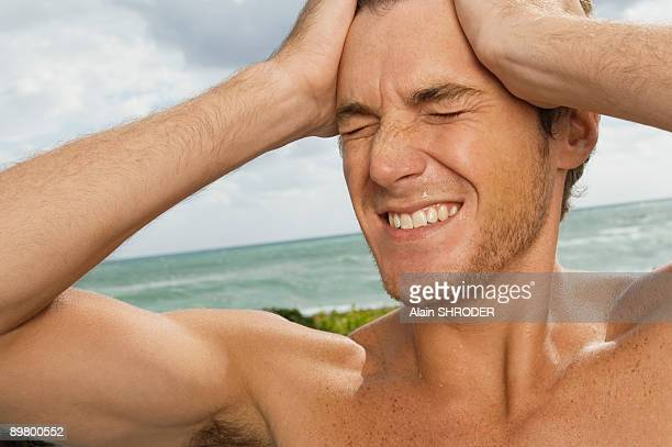 Man holding his head in pain on the beach