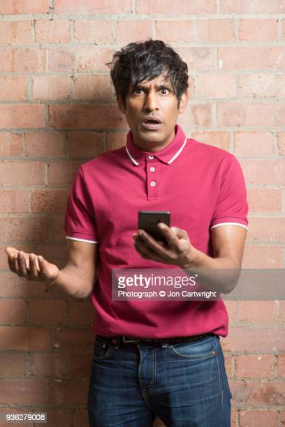 Man holding his phone looks at the camera with disbelief