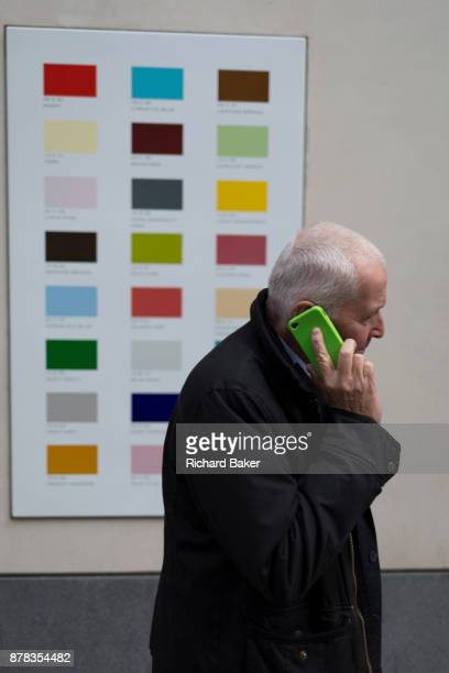 A man holding his phone walks with a green case walks past a colour swatch on the wall of a central London business on 22nd November 2017 in London...