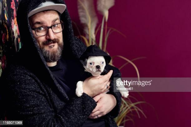 man holding his pug - representar fotografías e imágenes de stock