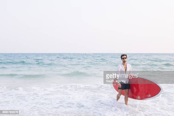 Man holding his surfboard