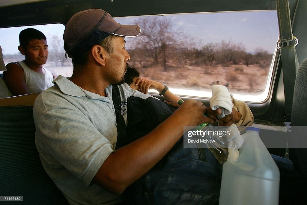 A man holding his water and backpack rides with other immigrants in a transport van on the dirt toll road that leads to the US-Mexico border on June 6, 2006 near Altar, Mexico, which is 60 miles south of the border village of Sasabe. More illegal immigrants pass through Altar where immigrant smuggling is the primary industry, than any other town. Available services include 'coyotes' or guides, transportation over 60 miles or more of dirt road in vans carrying as many as 25 people, about 150 'hospedajes' or guest houses, provisions, a free mobile clinic catering mostly to people who were hurt trying to cross the border, and groups who warn immigrants on the dangers of the trek and help those in need. From here, most immigrants are guided through Sasabe, where nightly robberies have become an industry and rape is common, then across the US-Mexico border to walk for about 45 miles through the desert before being picked up by smuggler vehicles. It is during the walk that most of the 473 deaths of 2005 occurred, mostly from exposure to extreme heat and fatigue.