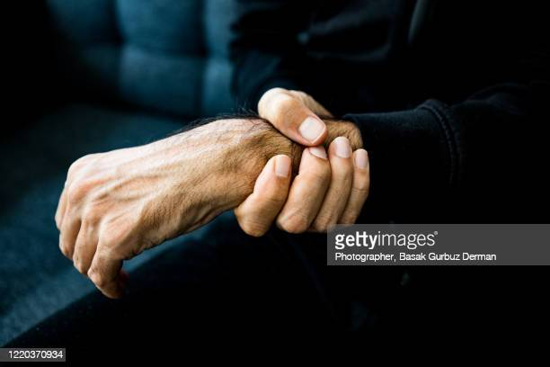a man holding his wrist, feeling pain - human arm stock pictures, royalty-free photos & images