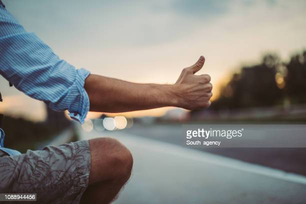 man holding hitchhiking thumb up - hitchhiking stock pictures, royalty-free photos & images