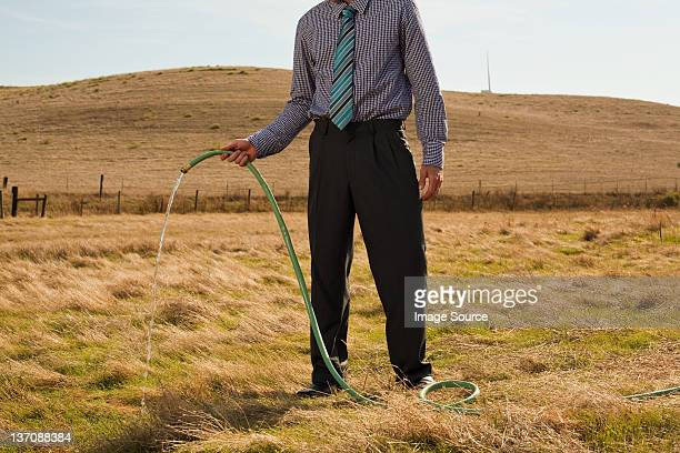 Man holding hose pipe in arid landscape