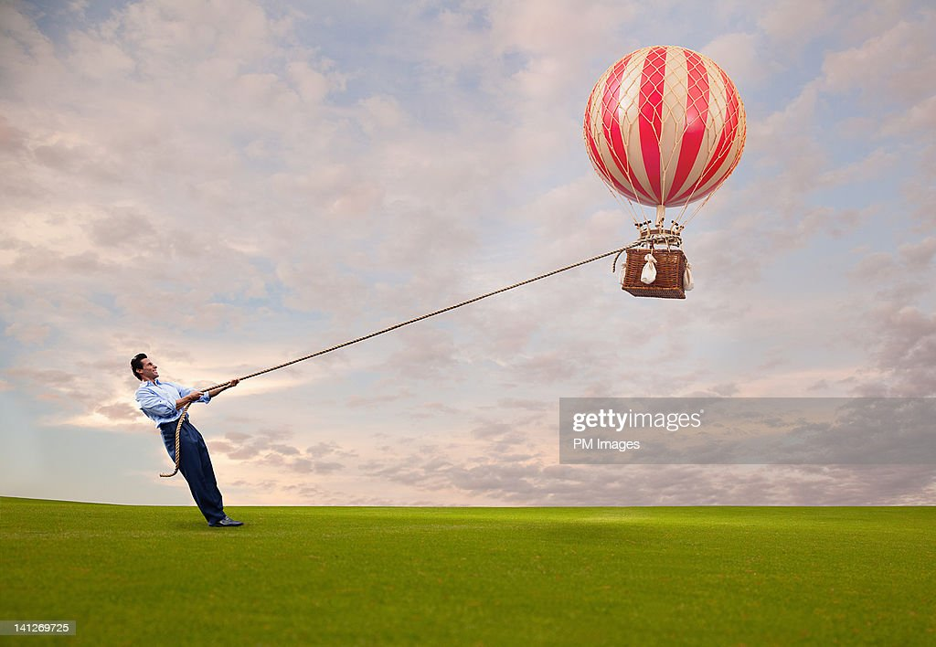 Man holding hot air balloon : Stock Photo