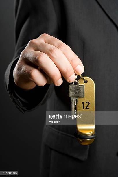 a man holding hotel key - hotel key stock photos and pictures