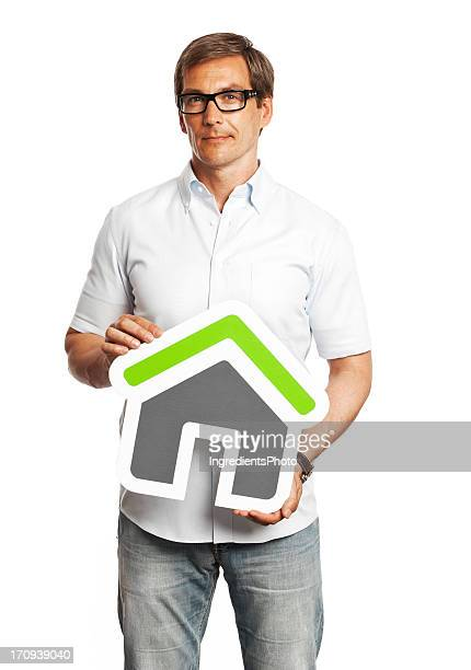 Man holding house sign isolated on white background.