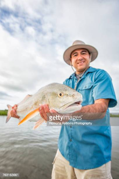 man holding huge redfish - redfish stock photos and pictures