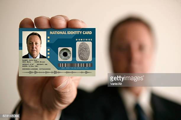 man holding identity card - identity card stock pictures, royalty-free photos & images