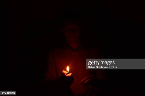 man holding illuminated cigarette lighter in darkroom - cigarette lighter stock pictures, royalty-free photos & images