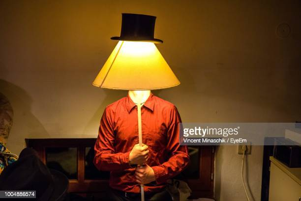 Man Holding Illuminated Lamp With Hat In Front Of Face At Home