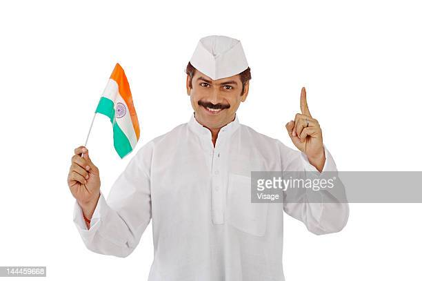 Man holding Indian flag, pointing his finger upwards