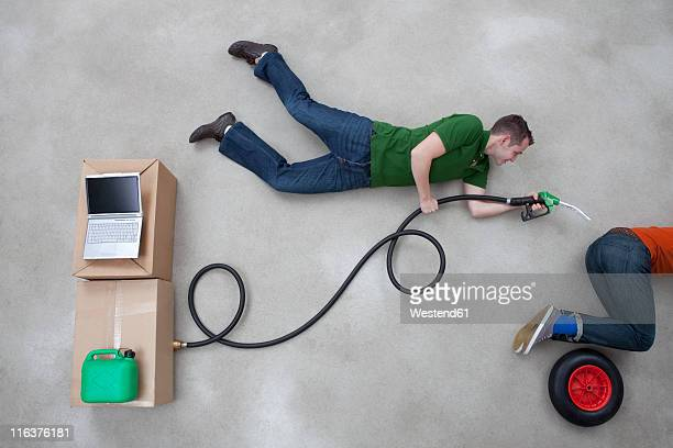 Man holding industrial hose with other man on automotive