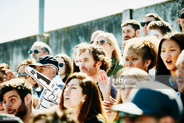 man holding inflatable number one finger in crowd - foam finger stock photos and pictures