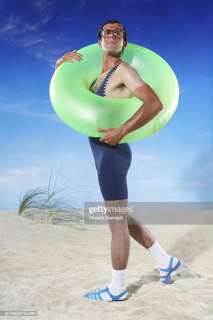 Man holding inflatable ring on beach : Stock Photo