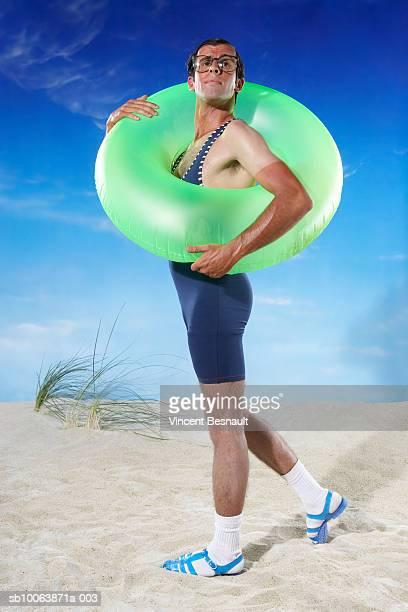 man holding inflatable ring on beach - homem moreno imagens e fotografias de stock