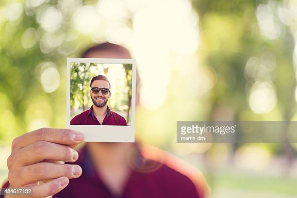Homme tenant un polaroid selfie