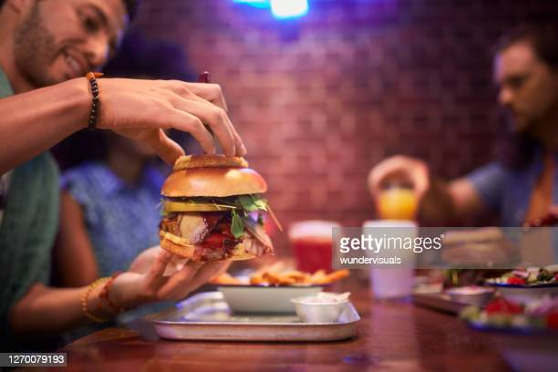 man holding juicy burger during friends meal in retro restaurant - succulent stock pictures, royalty-free photos & images