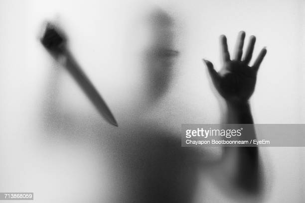 man holding knife seen through glass - mord stock-fotos und bilder