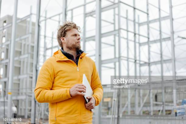 man holding laptop, construction site in the background - kontrolle stock-fotos und bilder