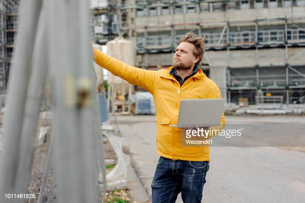 man holding laptop, construction site in the background - ruhr stock pictures, royalty-free photos & images