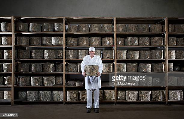 Man holding large cheese in front of rack of cheese.