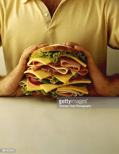 man holding large sandwich -  firak stock pictures, royalty-free photos & images