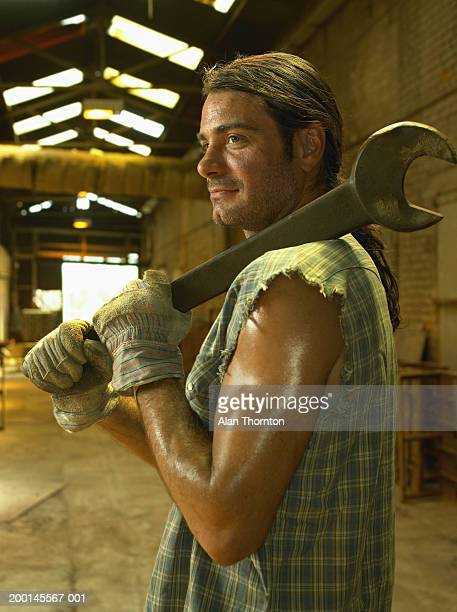 Man holding large wrench over shoulder, side view