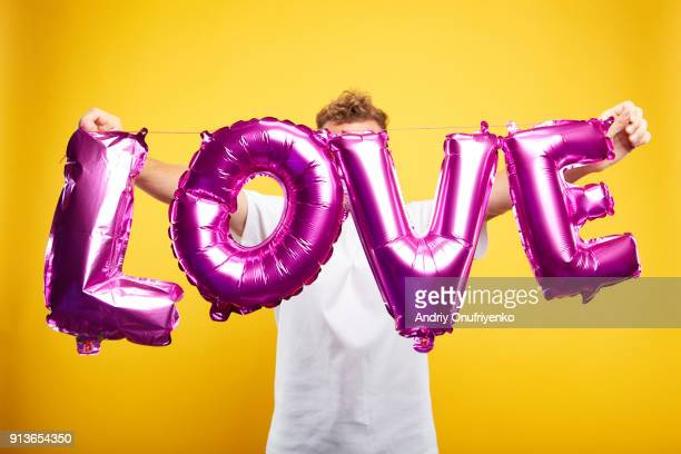 man holding letters on color background - rose photos et images de collection