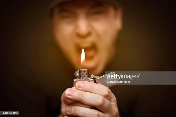 Man holding lit glowing lighter