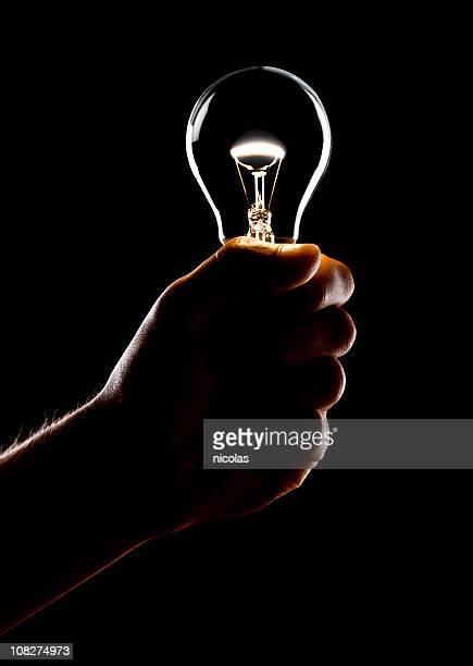 Mann hält beleuchteten Glühbirne, Low key