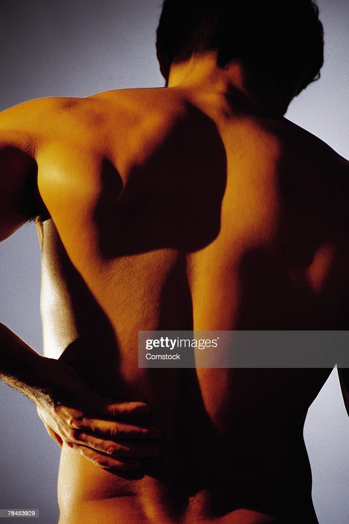 Man holding lower back in pain : Stockfoto