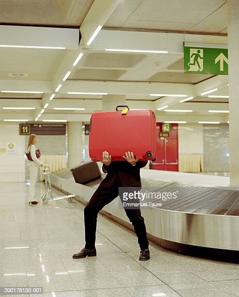 Man holding luggage at baggage claim in airport woman in background
