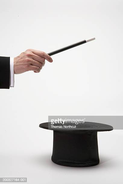 Man holding magic wand over top hat, close-up of hand, side view