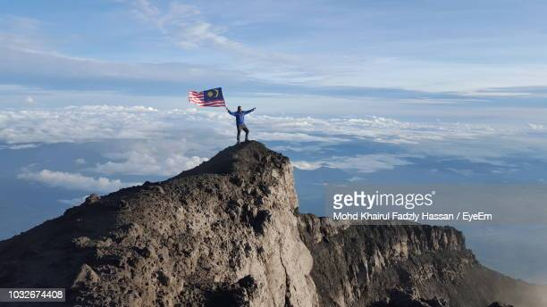 man holding malaysian flag while standing on mountain against cloudy sky - 旗 ストックフォトと画像