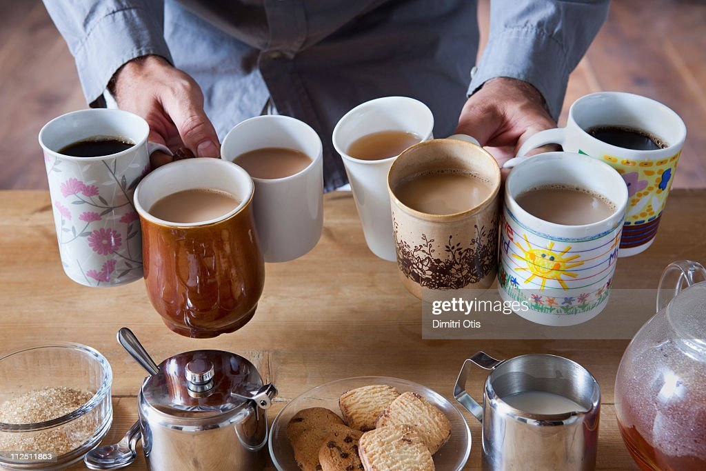 Man holding many tea and coffee cups : Stock Photo