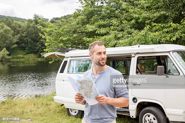 Man holding map at a van at lakeside