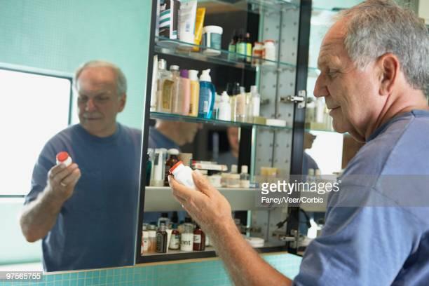man holding medicine bottle - armoire de toilette photos et images de collection