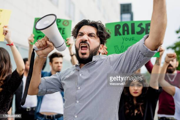 man holding megaphone screaming with protestors on street - campaigner stock pictures, royalty-free photos & images