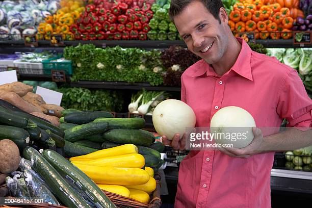man holding melons against chest, smiling, portrait, close-up - produce aisle stock photos and pictures