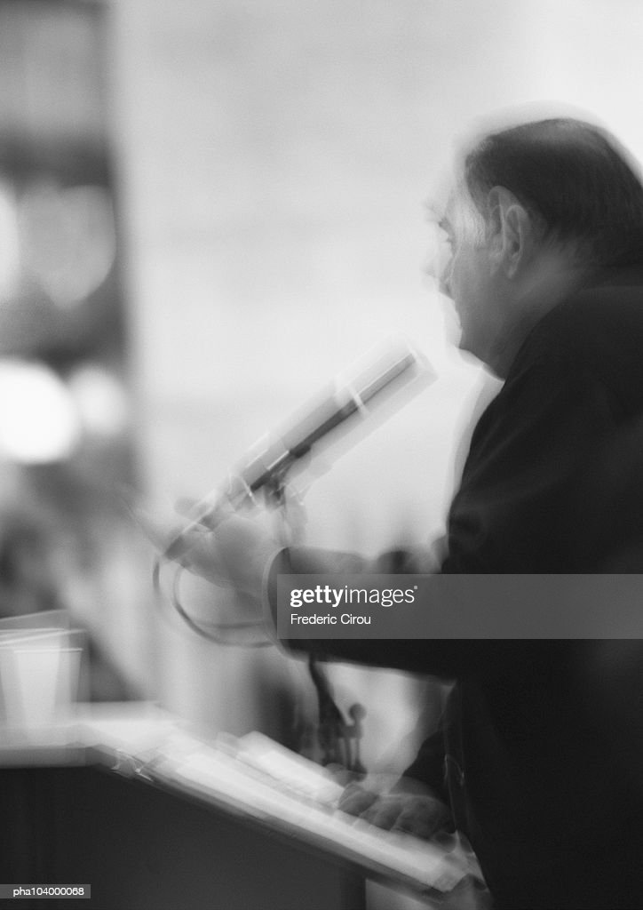 Man holding microphone, blurred, b&w : Stockfoto
