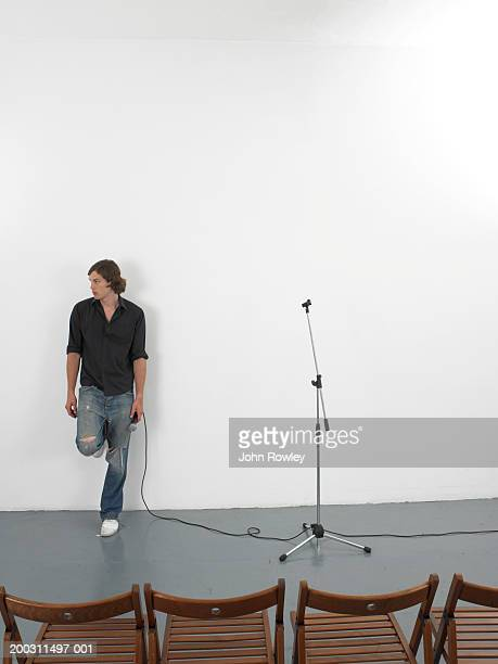 man holding microphone, leaning against wall looking to one side - microphone stand stock photos and pictures