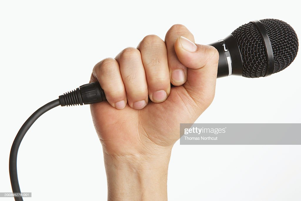 Man holding microphone (focus on microphone) : Stock Photo