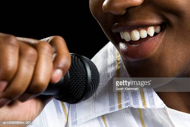 Man holding microphone to mouth, close-up