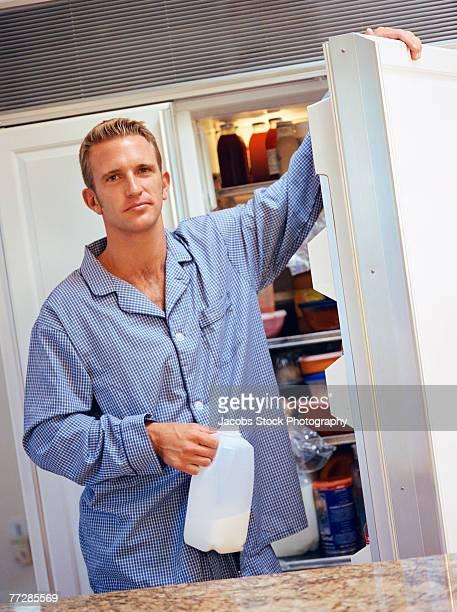 Man holding milk with open refrigerator door